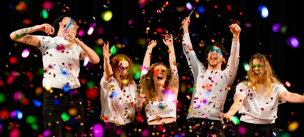 Five people in white shirts. They are laughing, cheering and throwing their hands in the air. They have masks painted on their faces and confetti is falling around them.